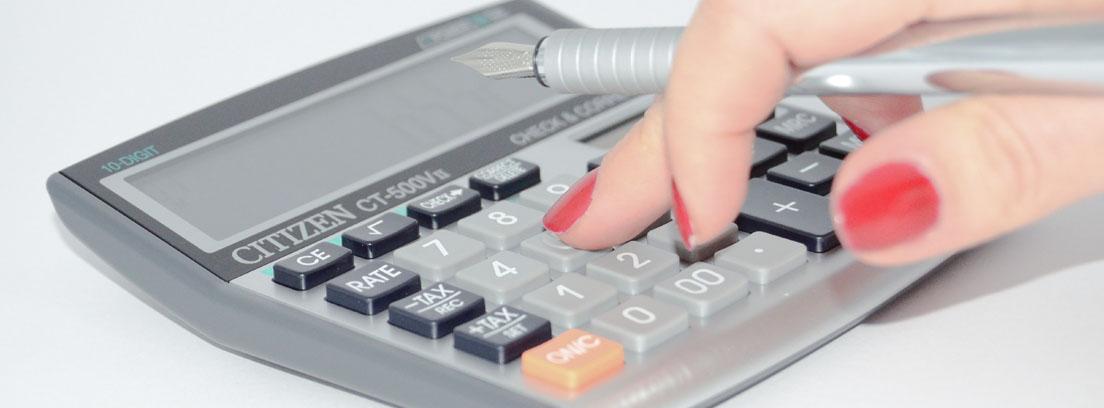Mano sujetando una pluma y pulsando los botones de una calculadora