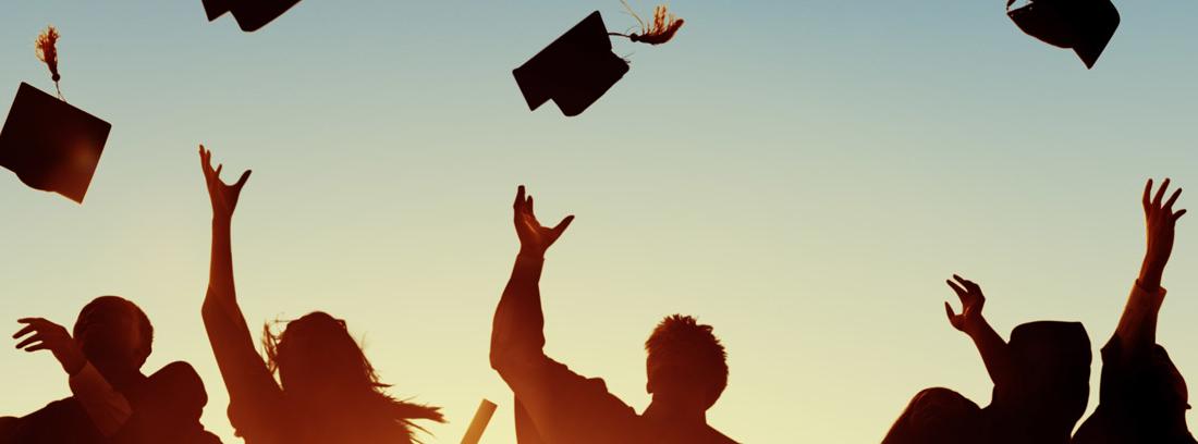 Universitarios lanzando sus birretes al aire