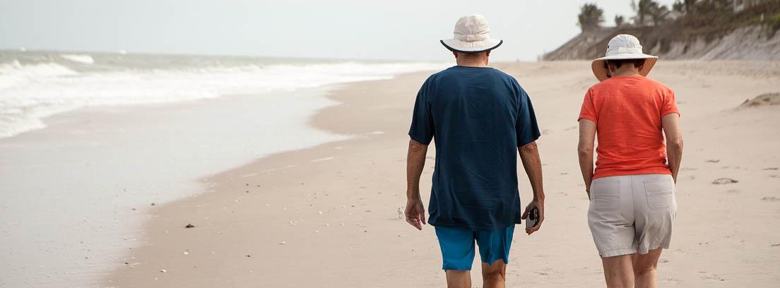 Hombre y mujer de espaldas paseando por la playa