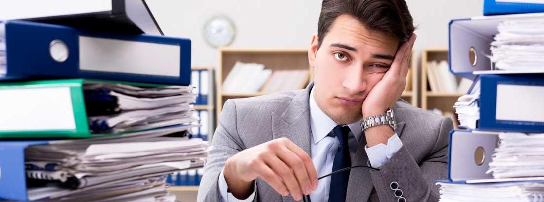 Hombre sentado a una mesa llena de archivadores con cara de cansado y aburrido