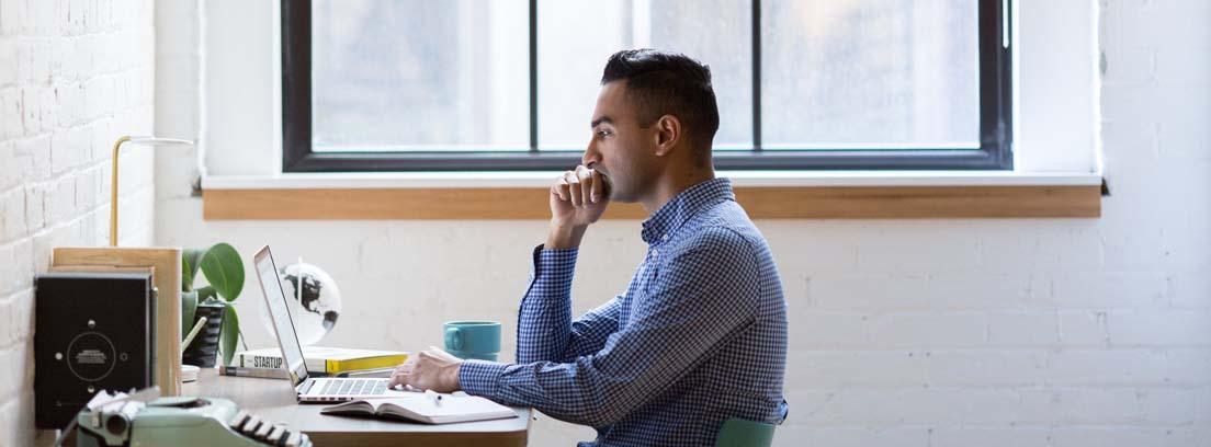 Hombre de perfil sentado a una mesa con un ordenador y una agenda, clave para mejorar el rendimiento en el trabajo