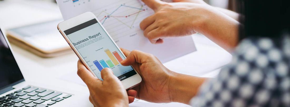 Manos sujetan tableta junta a otras con hojas con infografías de colores