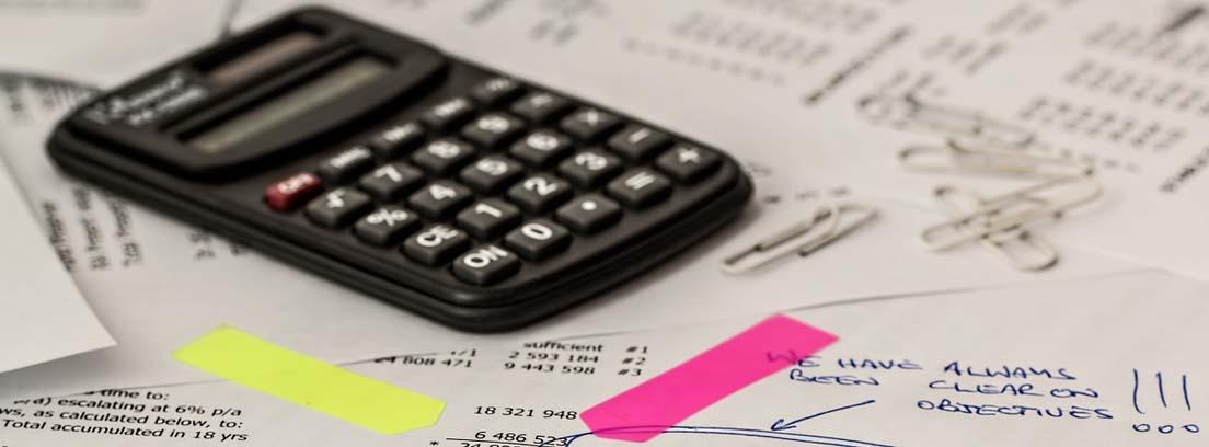 Calculadora, bolis y clip sobre papeles con cuentas y balances de contabilidad