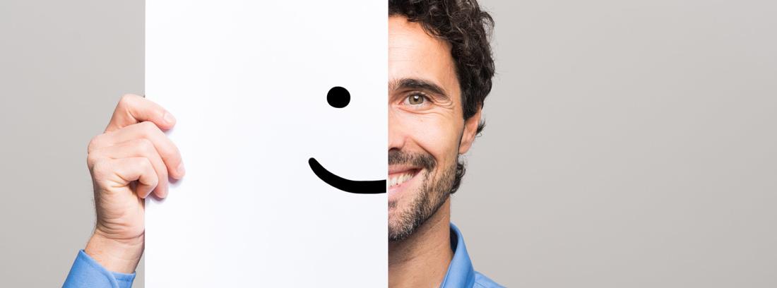 Hombre con gesto alegre tapándose media cara con un folio en el que hay dibujado un ojo y una boca sonriente