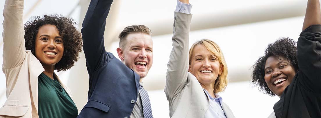 Un hombre y tres mujeres levantando un brazo con gesto alegre