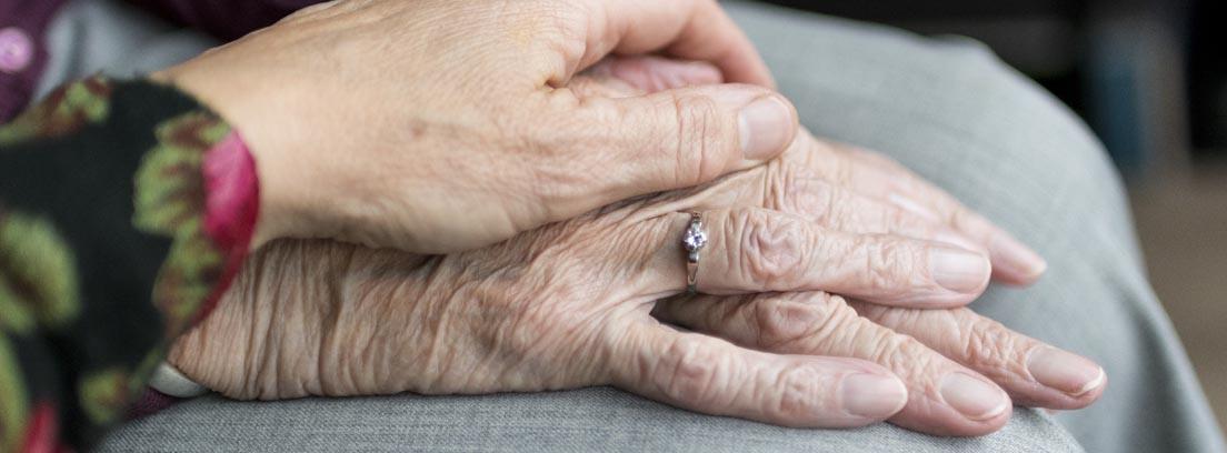 Una mano de mujer sobre otra mano de una persona mayor
