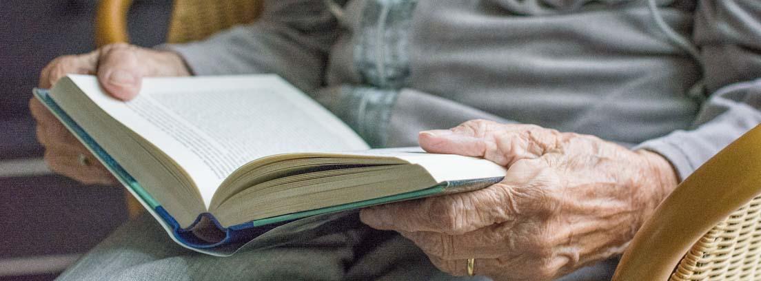 Manos de una persona mayor sosteniendo un libro en un centro de día para mayores