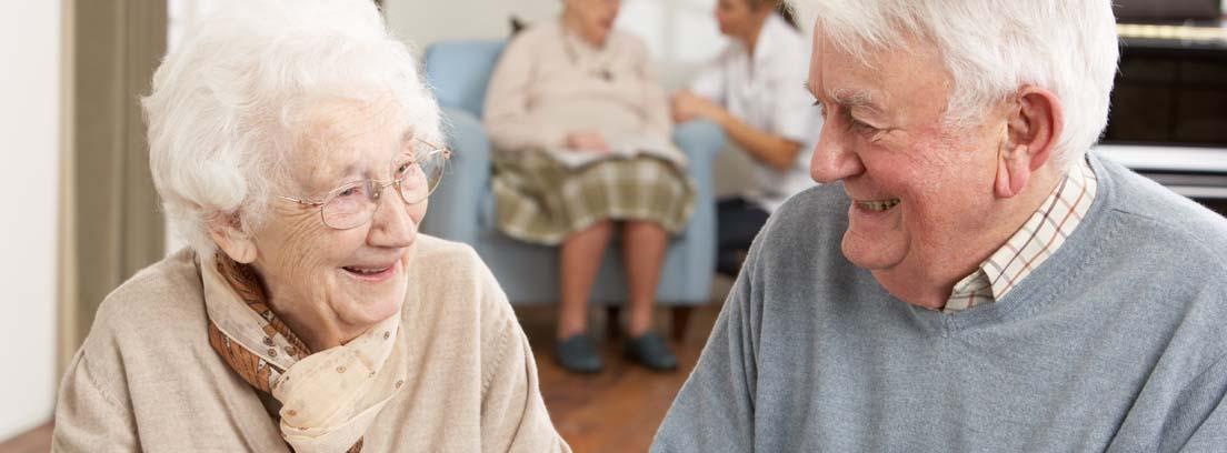 Hombre y mujer de avanzada edad sonrientes jugando al dominó en un centro de día para personas mayores