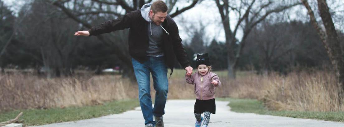 Padre corre con su hija pequeña de la mano