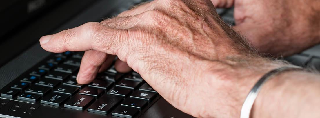 Manos de hombre mayor escribiendo sobre un teclado de ordenador