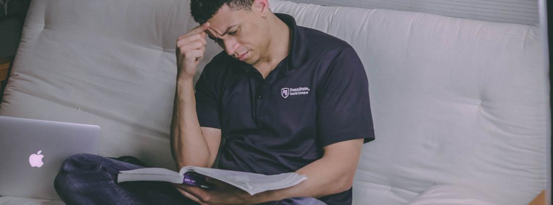Hombre sentado mira un libro con gesto de tener problemas económicos