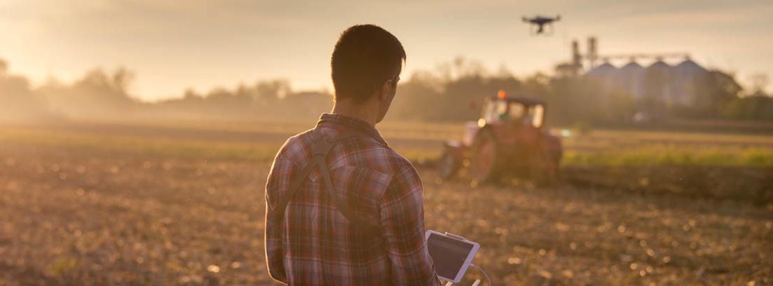 Hombre manejando un dron sobre un campo de cultivo