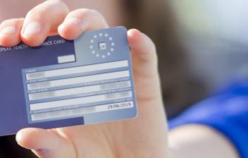 Mano extendida sujetando una tarjeta sanitaria europea