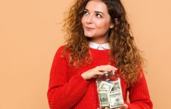 Chica sosteniendo un bote con dinero