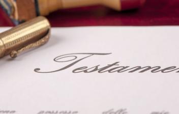 Papel con la palabra 'testamento', un boli y un sello de madera