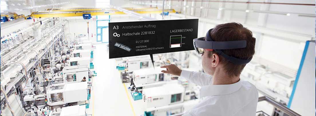 Mujer con gafas especiales tocando una pantalla holográfica en una industria
