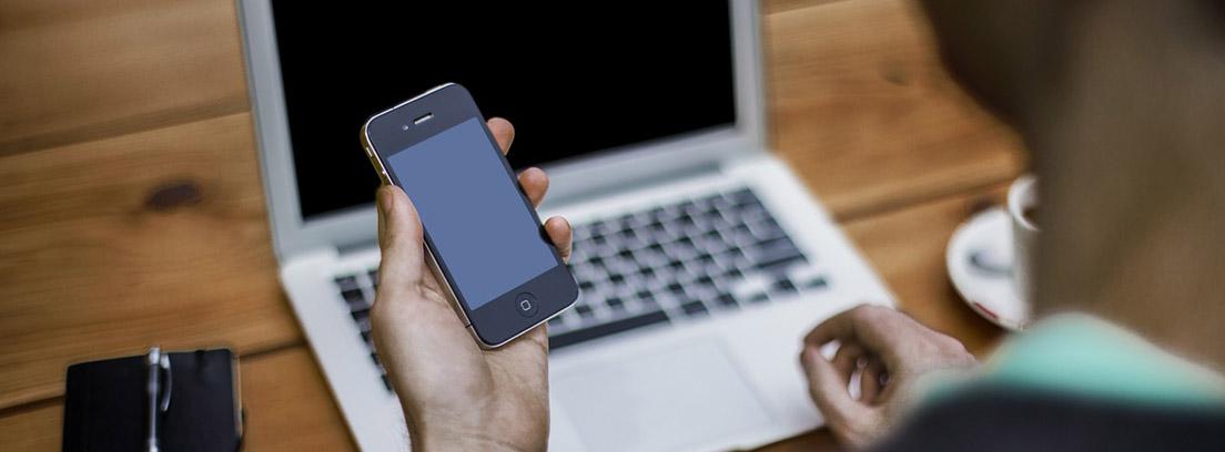 Persona con móvil en la mano y frente a portátil para consultar su estado en la Seguridad Social
