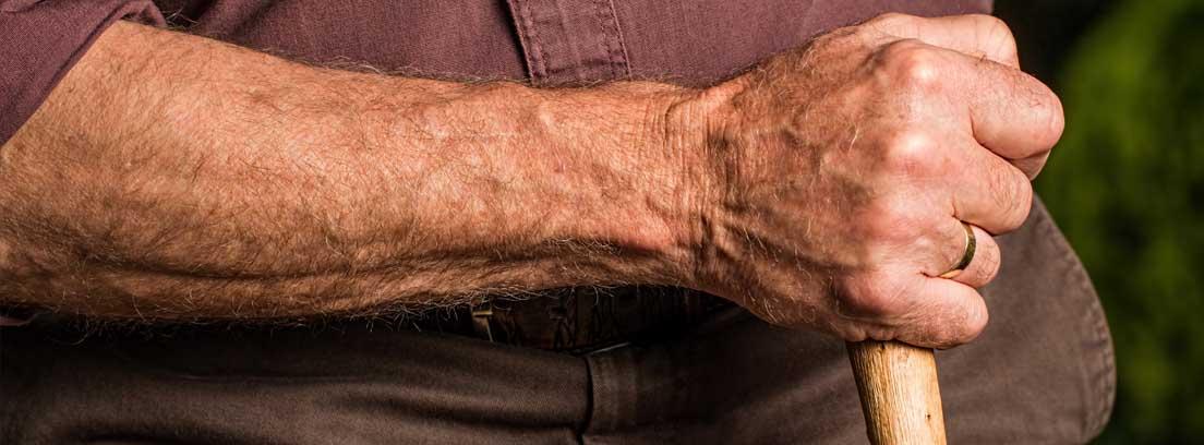 Primer plano de una mano de persona mayor con bastón para evitar caídas