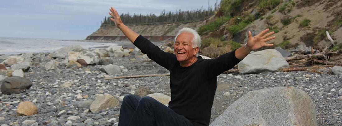 Hombre con pelo blanco extiende sus brazos al cielo con cara de felicidad