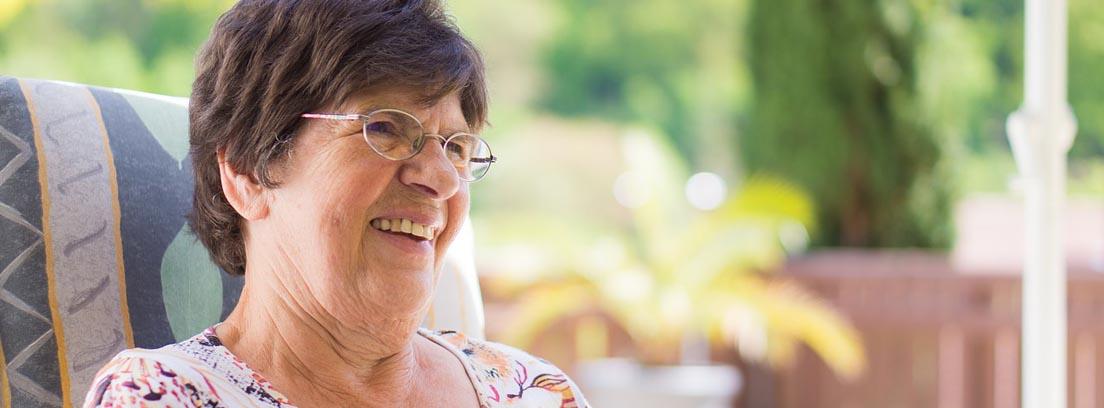Mujer mayor con gafas y gesto de felicidad