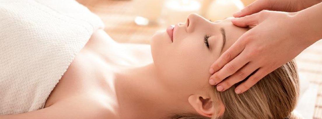 Mujer tumbada recibiendo un masaje facial