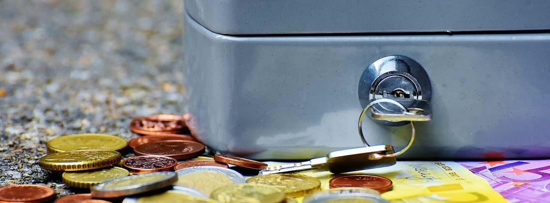 Caja metálica cerrada con una llave con billetes y monedas a su alrededor