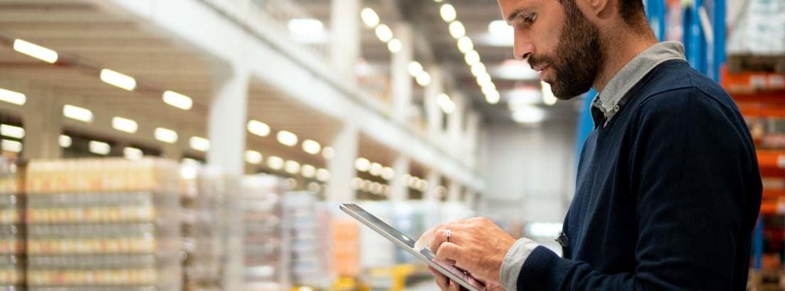 Hombre con tablet en la mano en un gran almacén con paquetes