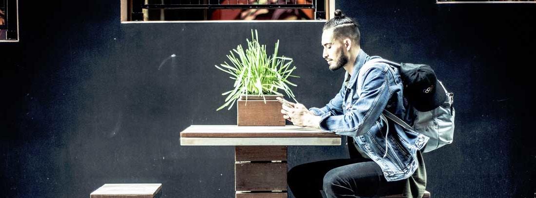 joven mirando su teléfono sentado en una mesa