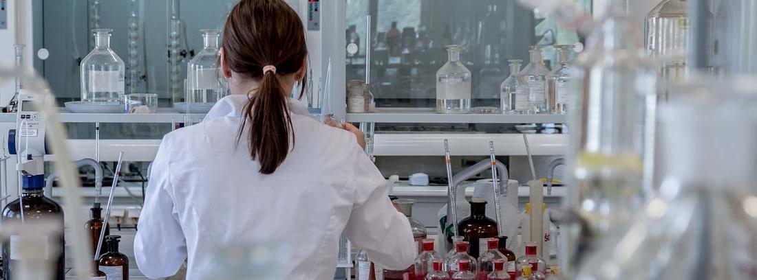 Mujer con bata blanca en laboratorio de investigación de enfermedades