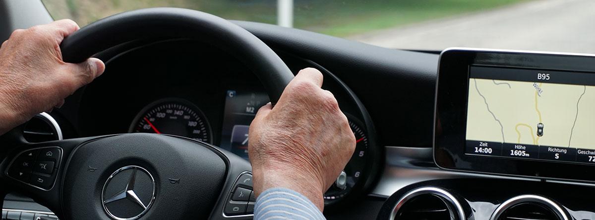 Manos de una persona mayor sobre el volante de un coche Mercedes