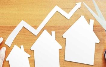 Manos con tijeras sobre una mesa en la que hay tres casas de papel de diferente tamaño en sentido creciente, como símbolo de la evolución del precio de la vivienda