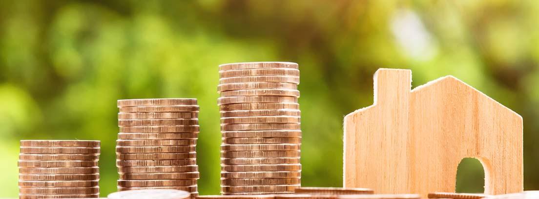 Tres columnas de monedas y una casita de madera como símbolo de la evolución del precio de la vivienda