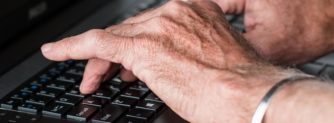Manos de un jubilado sobre el teclado de un ordenador para buscar un club de jubilados