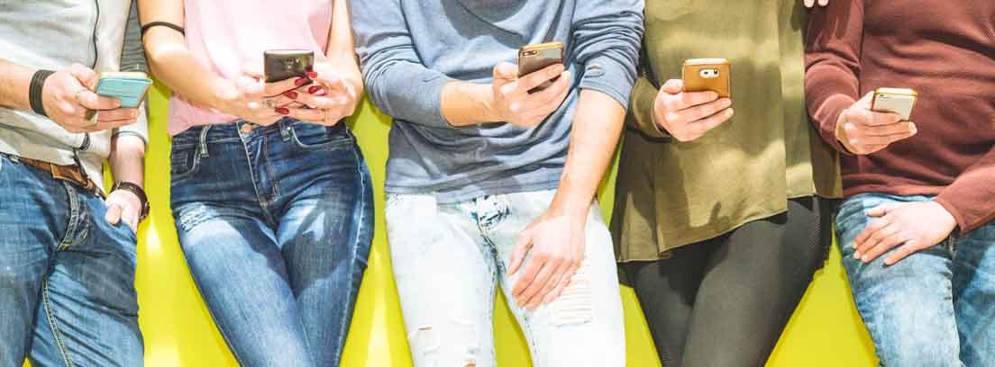 Varias personas de pie usando un teléfono móvil