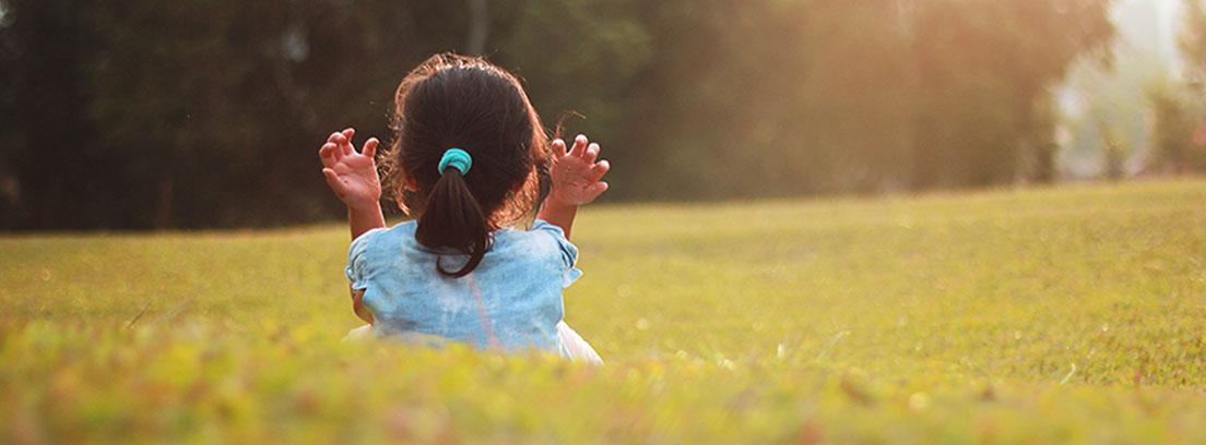 Niña pequeña de espaldas sentada en mitad del campo