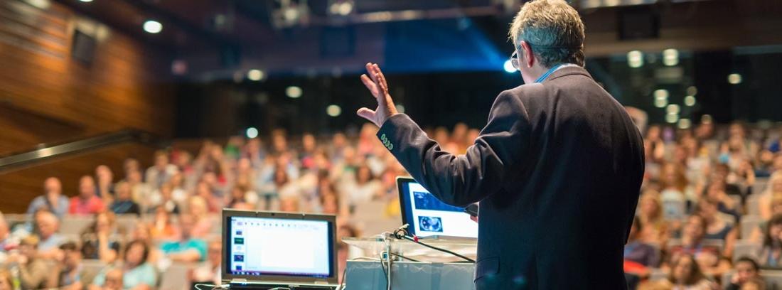 hombre dando una conferencia ante un auditorio lleno de personas