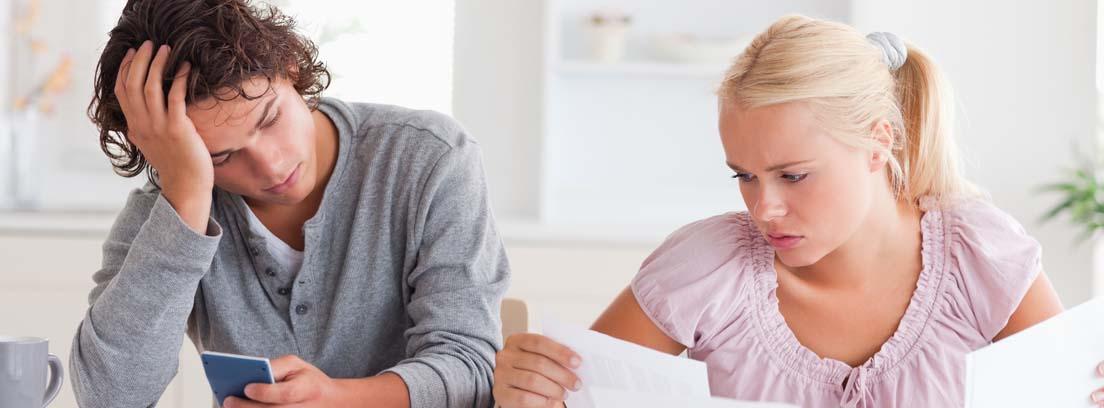 Hombre y mujer con gesto preocupado consultando unos papeles y el móvil
