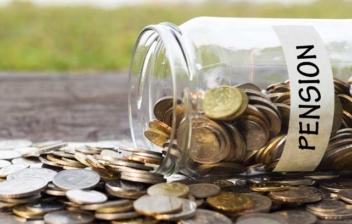 Bote de cristal con la palabra 'pension' tirado y un montón de monedas saliendo de su interior