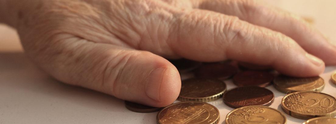 Mano de una persona mayor sobre unas monedas de Euro