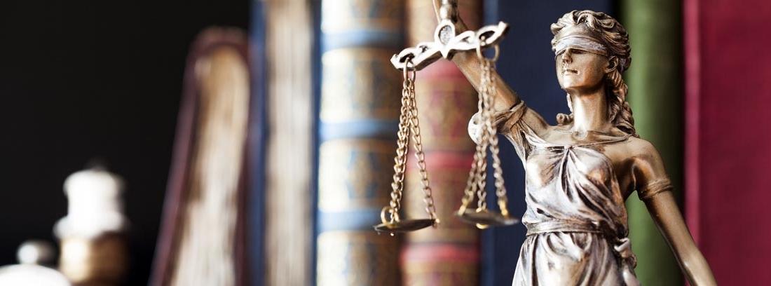 Estatua de la justicia en un estante con libros