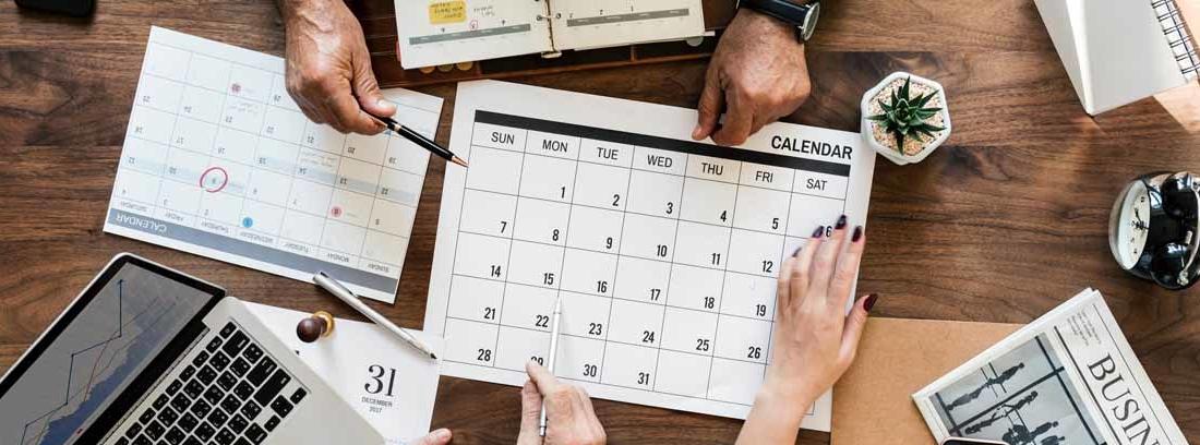 Manos sobre un calendario señalando diferentes días hábiles