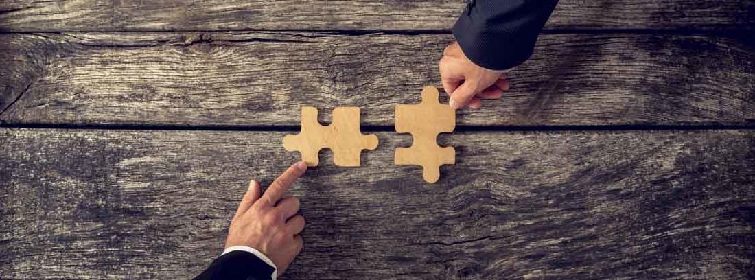 Una mano acerca una pieza de puzle a otra que sujeta otra mano