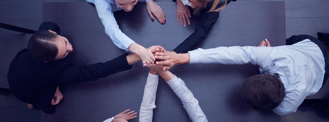 Imagen cenital de varias personas uniendo sus manos