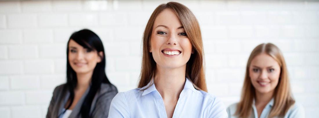 Tres mujeres sonrientes con los brazos cruzados