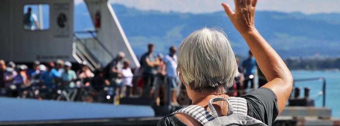 Persona de pelo blanco de espaldas con mano levantada delante de un barco