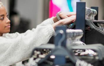 Mujer con manos sobre barra con muchas perchas con ropa