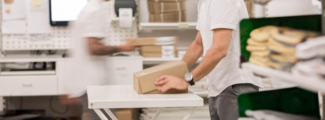 Hombre cerrando una caja junto sobre una mesa junto a estantes con paquetes
