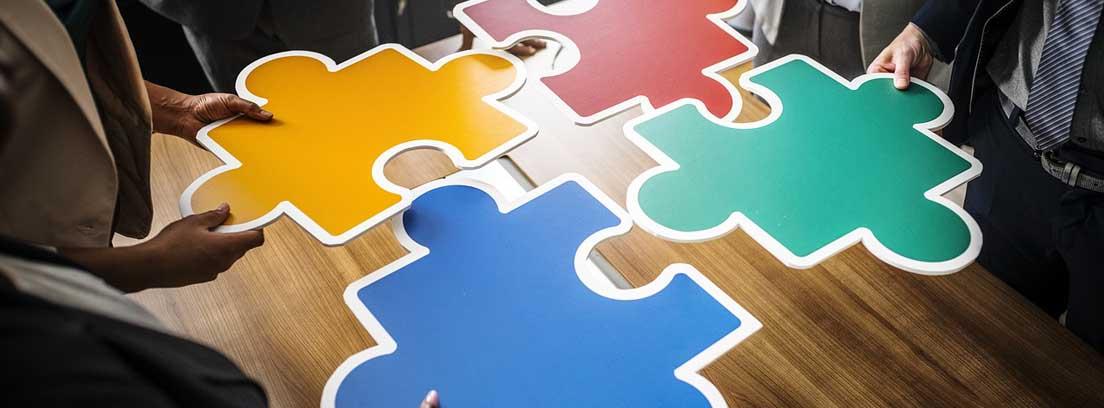 Manos sujetan 4 piezas de puzzle grandes y de diferentes colores