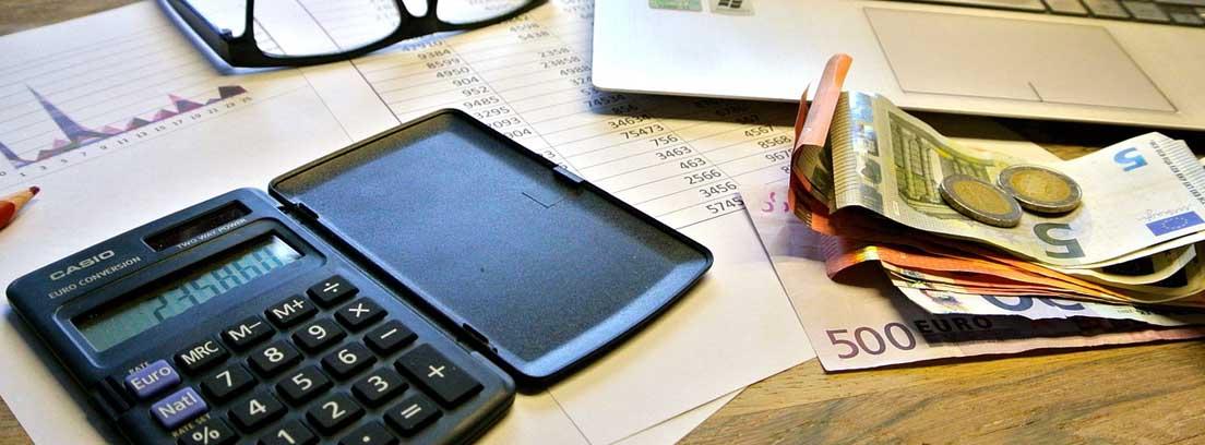 Calculadora sobre papeles junto a portátil y dinero