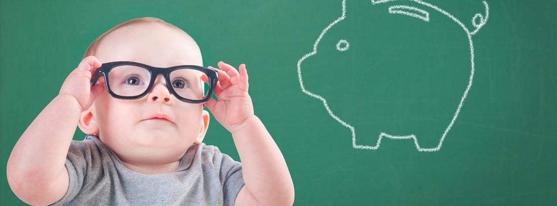Bebé con gafas de pasta delante de una pizarra con una hucha pintada